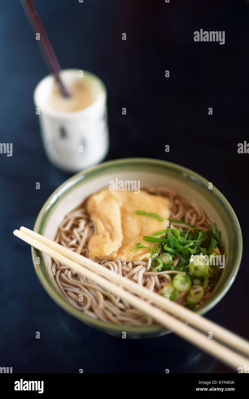 Bowl of Ramen with Soba noodles and tofu and Amazake drink on a table in a Japanese restaurant, Kyoto, Japan. - Stock Image