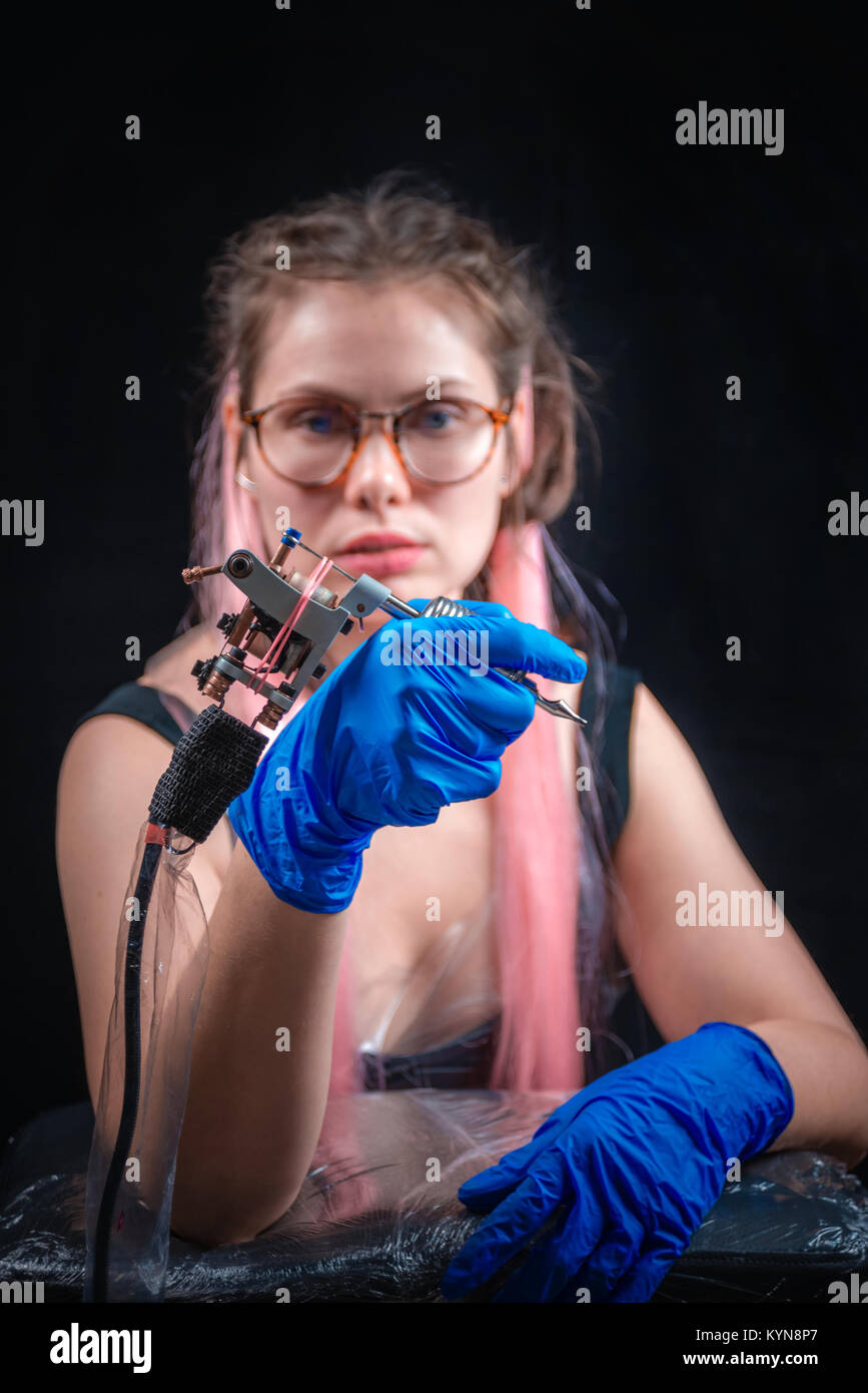 Master of the art of tattooing and a tattoo machine in tattoo studio - Stock Image