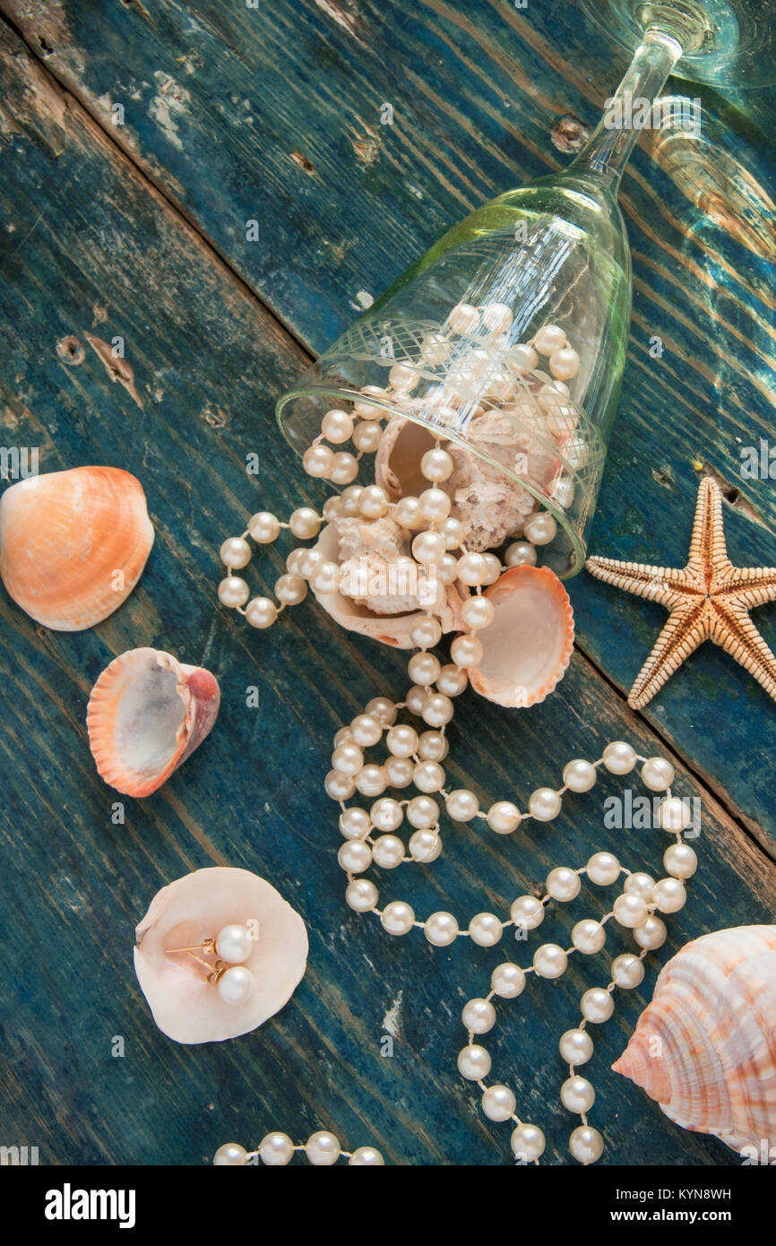 The pirate's treasure - white pearls and shells on blue wooden background, vintage fashion concept - Stock Image