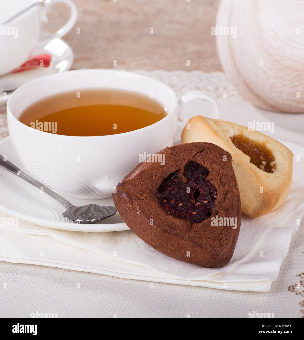 Raspberry and apricot filled hamantash cookies and cup of tea - Stock Image