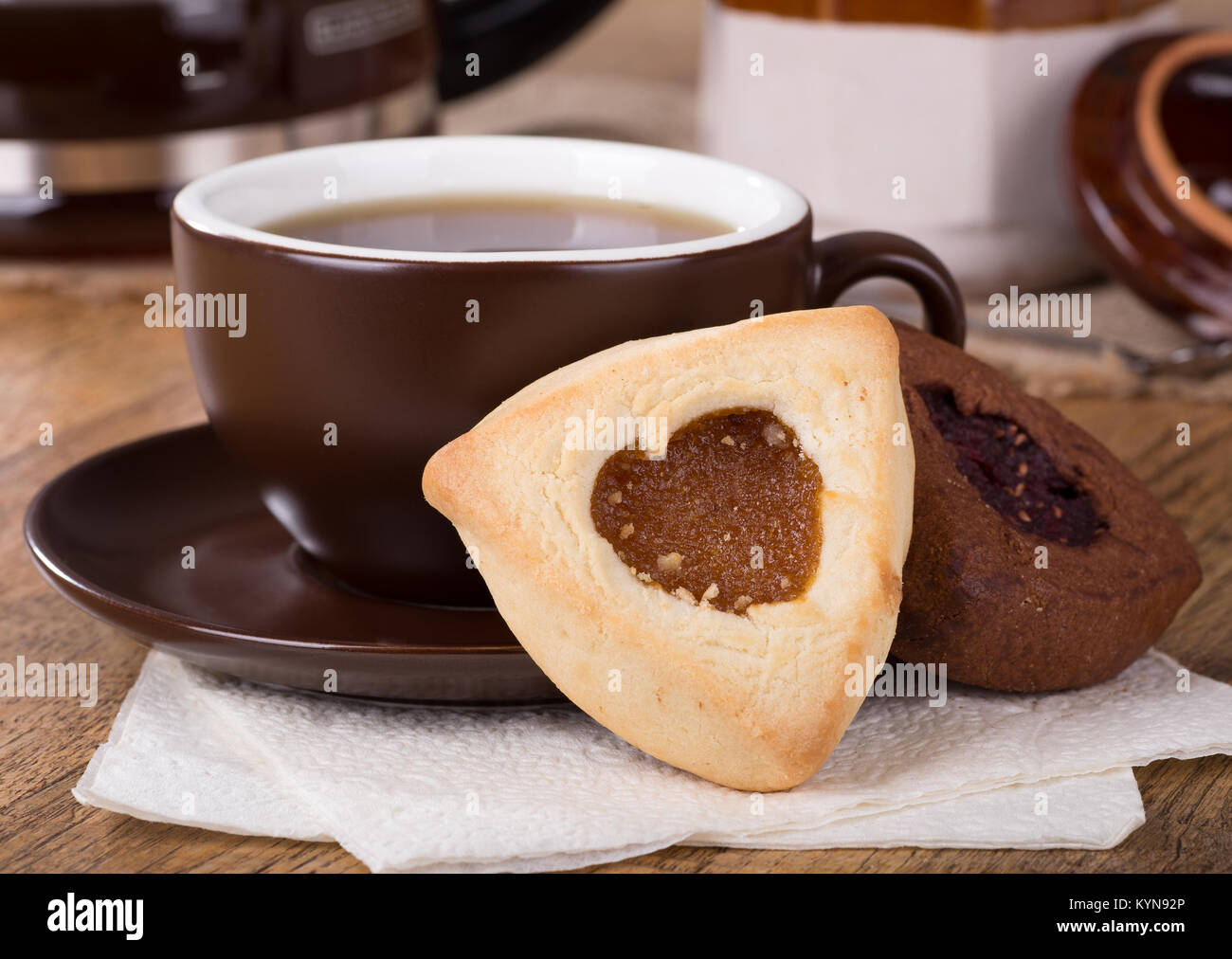 Closeup of an apricot filled hamantash cookie and cup of coffee - Stock Image