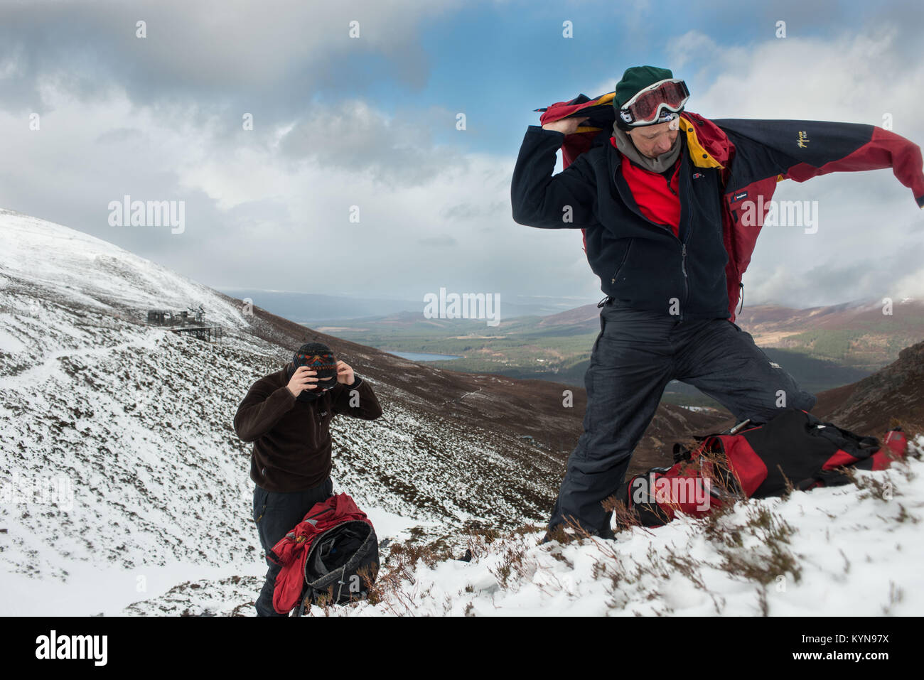 Winter Skills training in Cairngorm Mountains prior to Snow holing trip. Whenever you stop putting on an extra layer - Stock Image