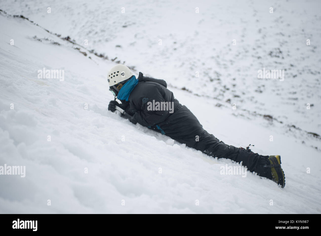 Winter Skills training in Cairngorm Mountains prior to Snow holing trip.  Mark stopping a slide wih his ice axe. - Stock Image