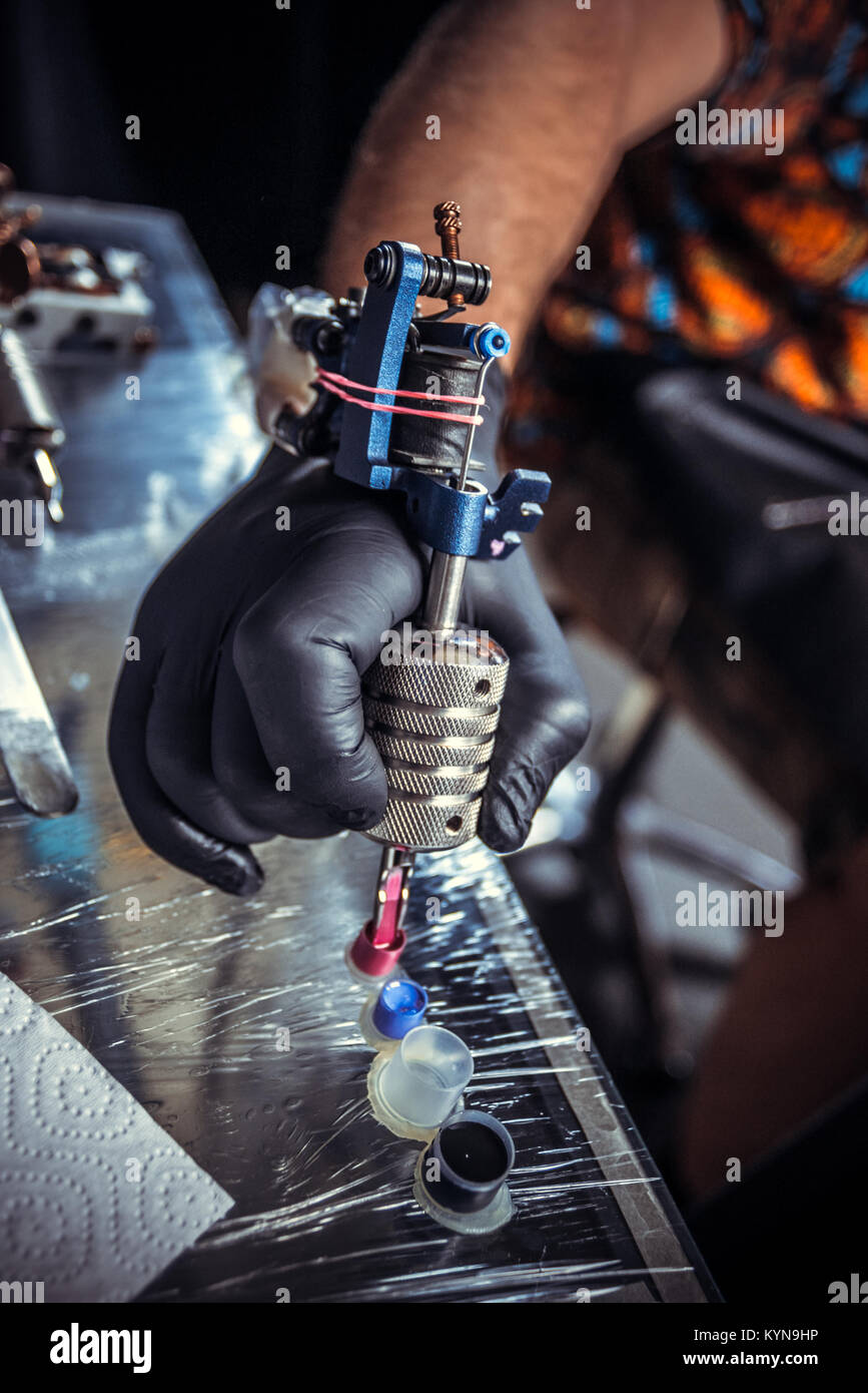 Hand of master of the art of tattooing with a tattoo gun. - Stock Image