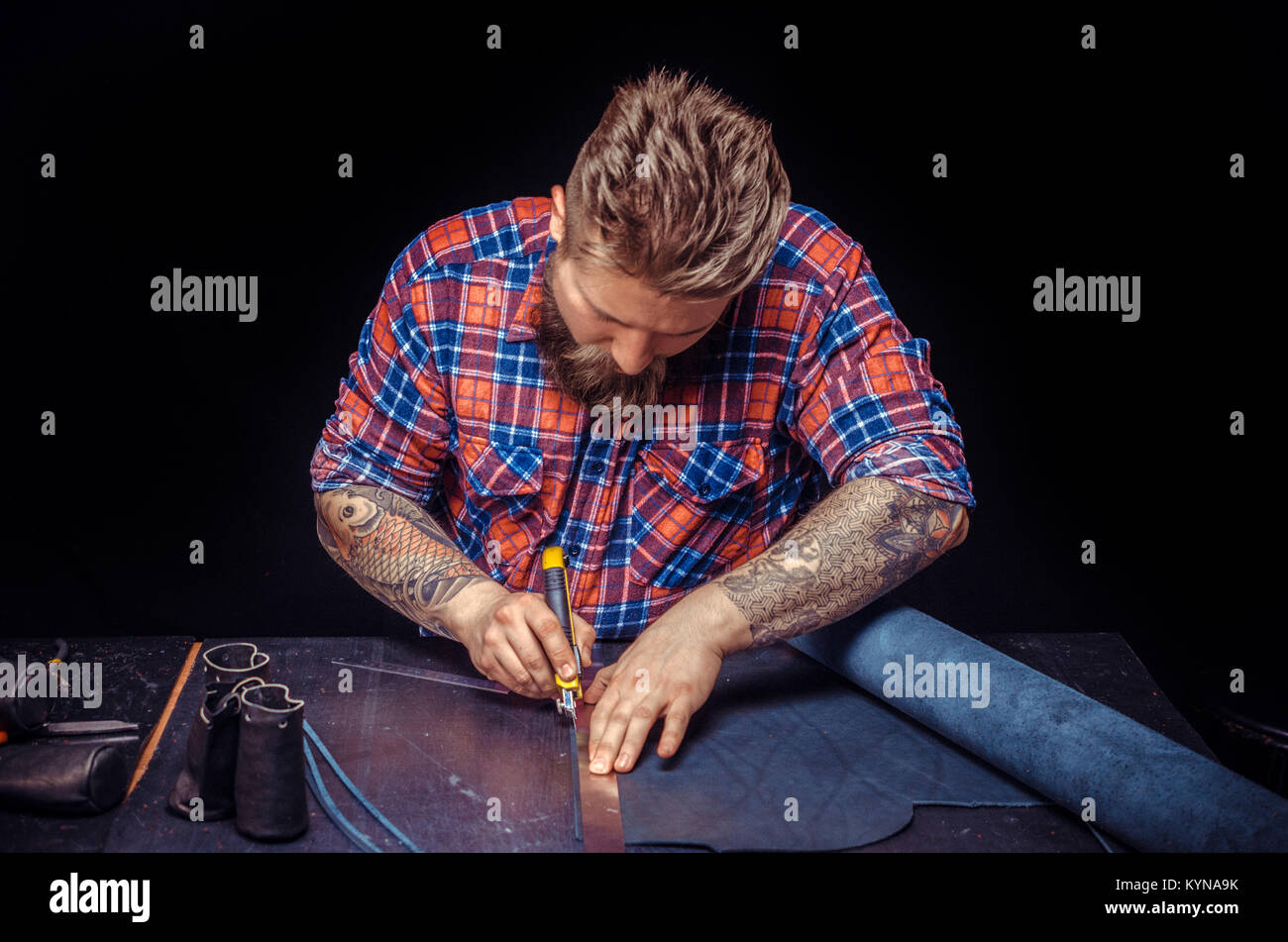 Craftsman performing leatherwork on a new product piece in the workplace - Stock Image