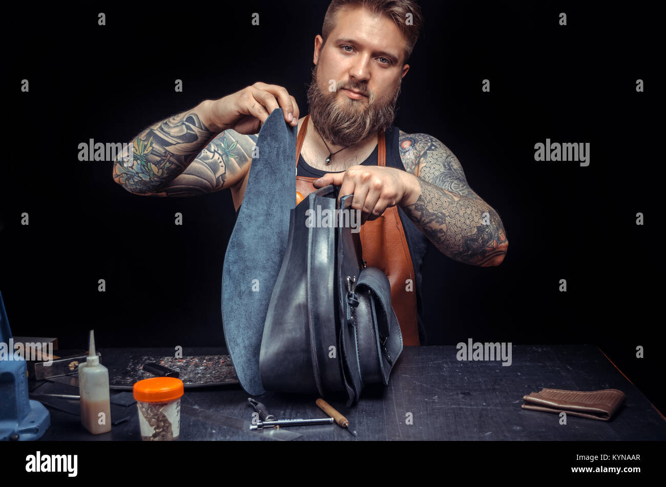 Worker of leather working with leather using crafting tools at a workshop - Stock Image