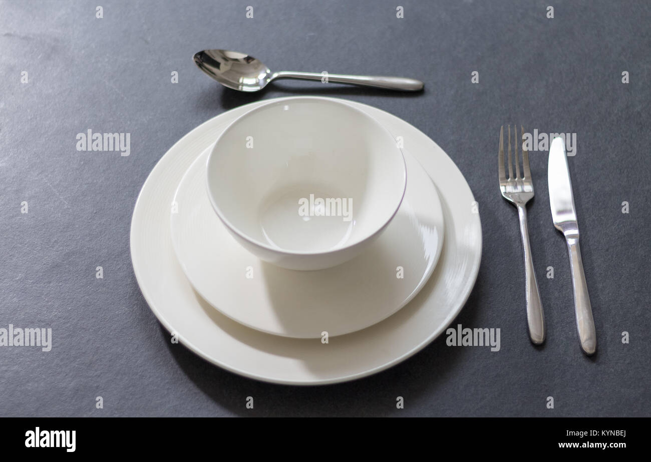 Table setting with dinner plate empty round white plate on dark background with cutlery & Table setting with dinner plate empty round white plate on dark ...