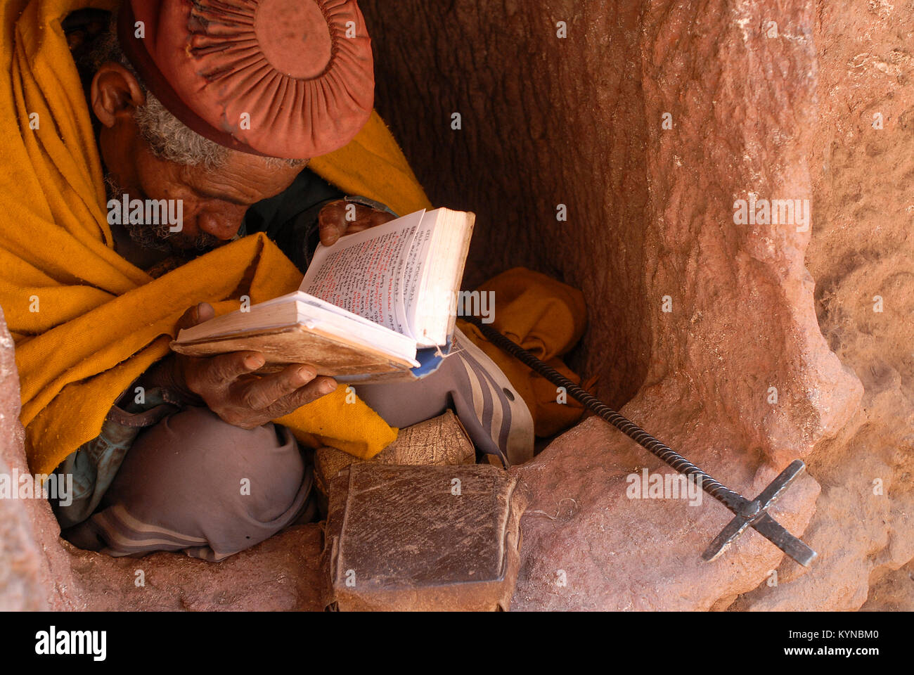 ETHIOPIA, Lalibela, rock churches built by King Lalibela 800 years ago, hermit sitting in tiny cave reading the - Stock Image