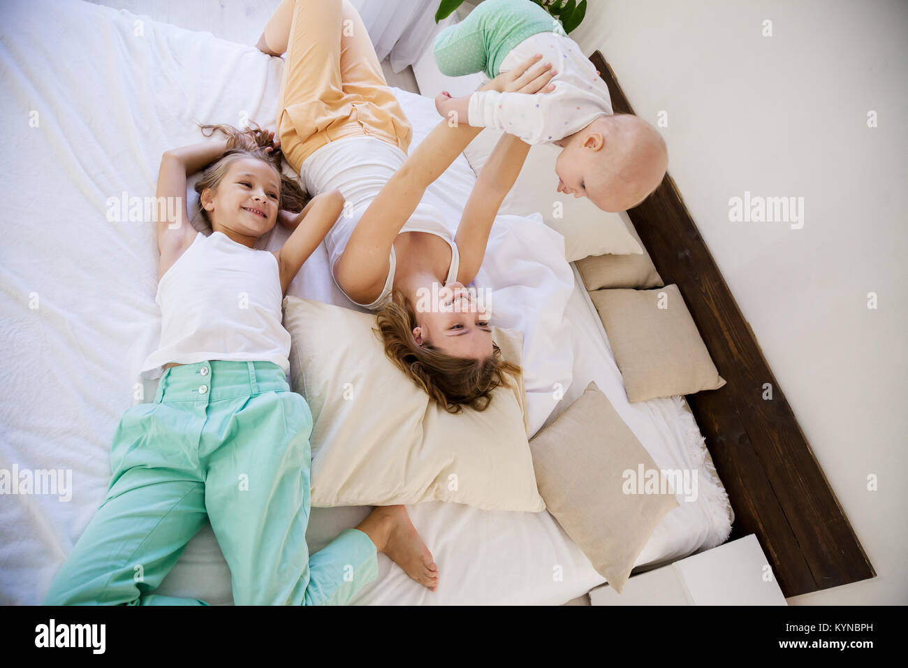 children of three sisters in the morning on the bed in the bedroom - Stock Image