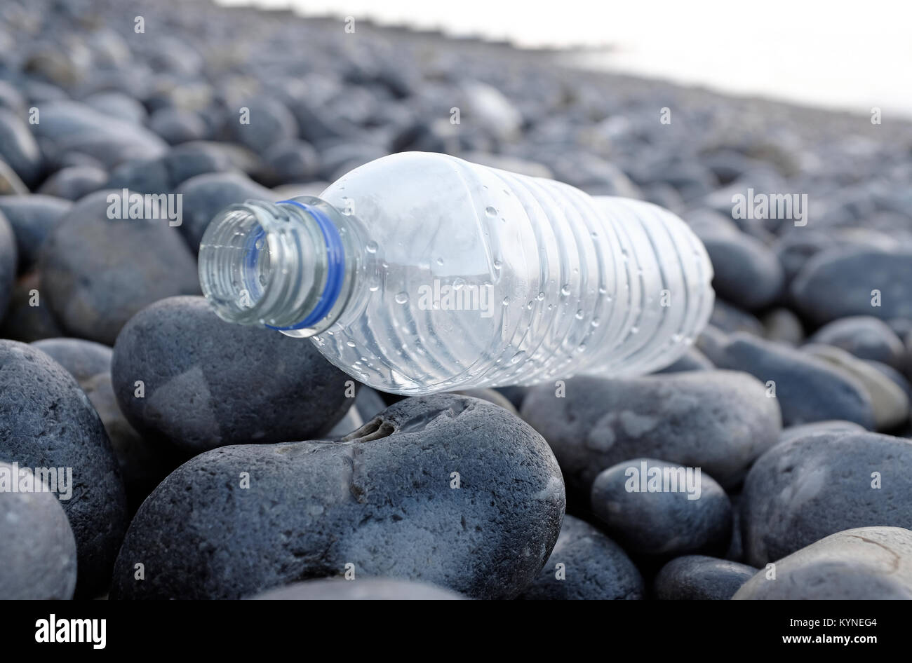 plastic water bottle washed up on shingle beach, sheringham, north norfolk, england - Stock Image