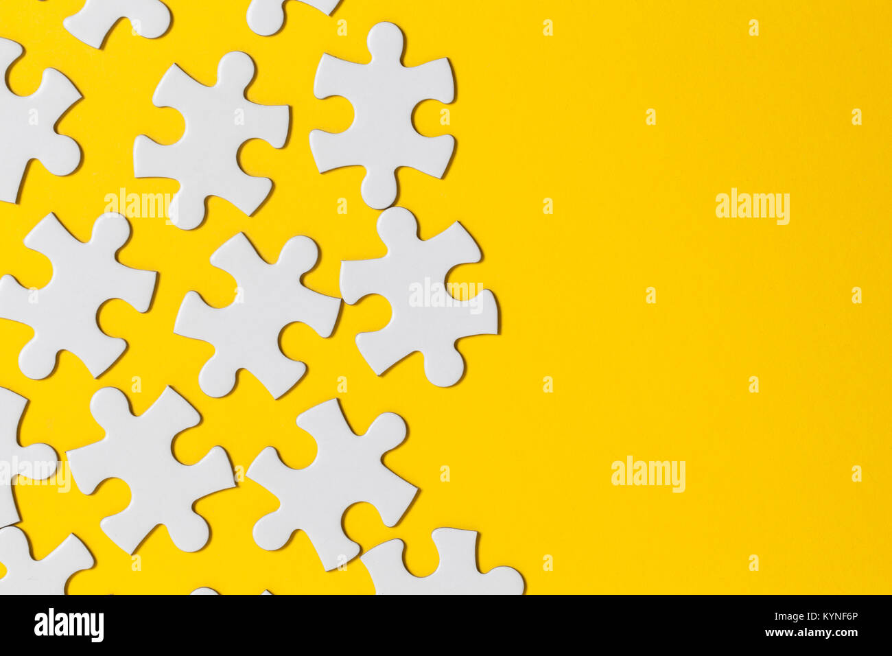 White jigsaw puzzle pieces on a yellow background. Business solution concept - Stock Image