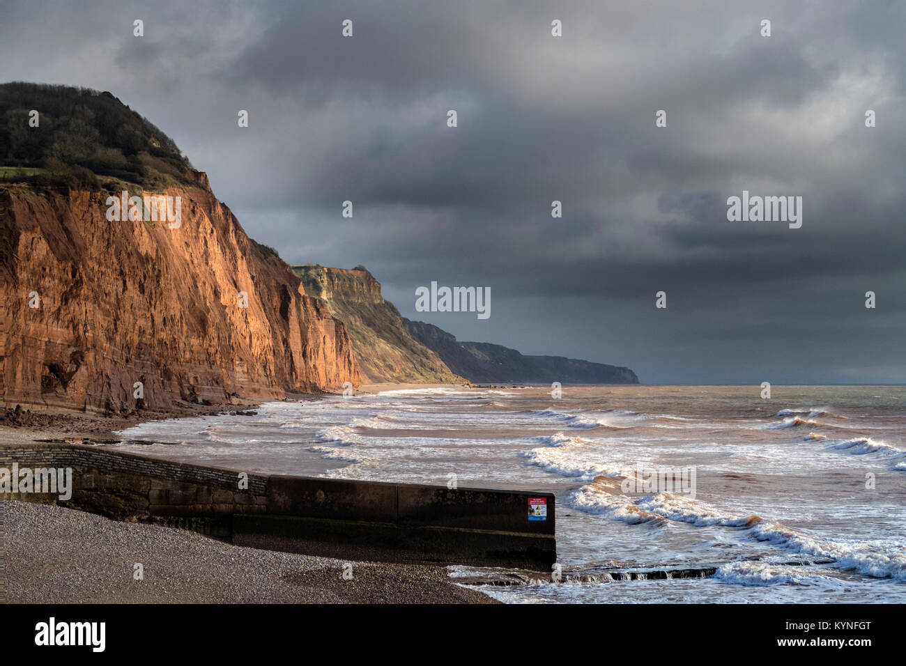 The crumbling red sandstone cliffs at Sidmouth, where serious rock falls occur each year,under dark skies - Stock Image