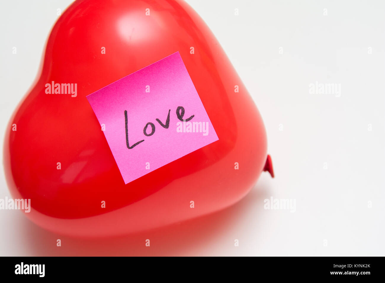 Love message for Valentines hand written note on a heart shape balloon - Stock Image