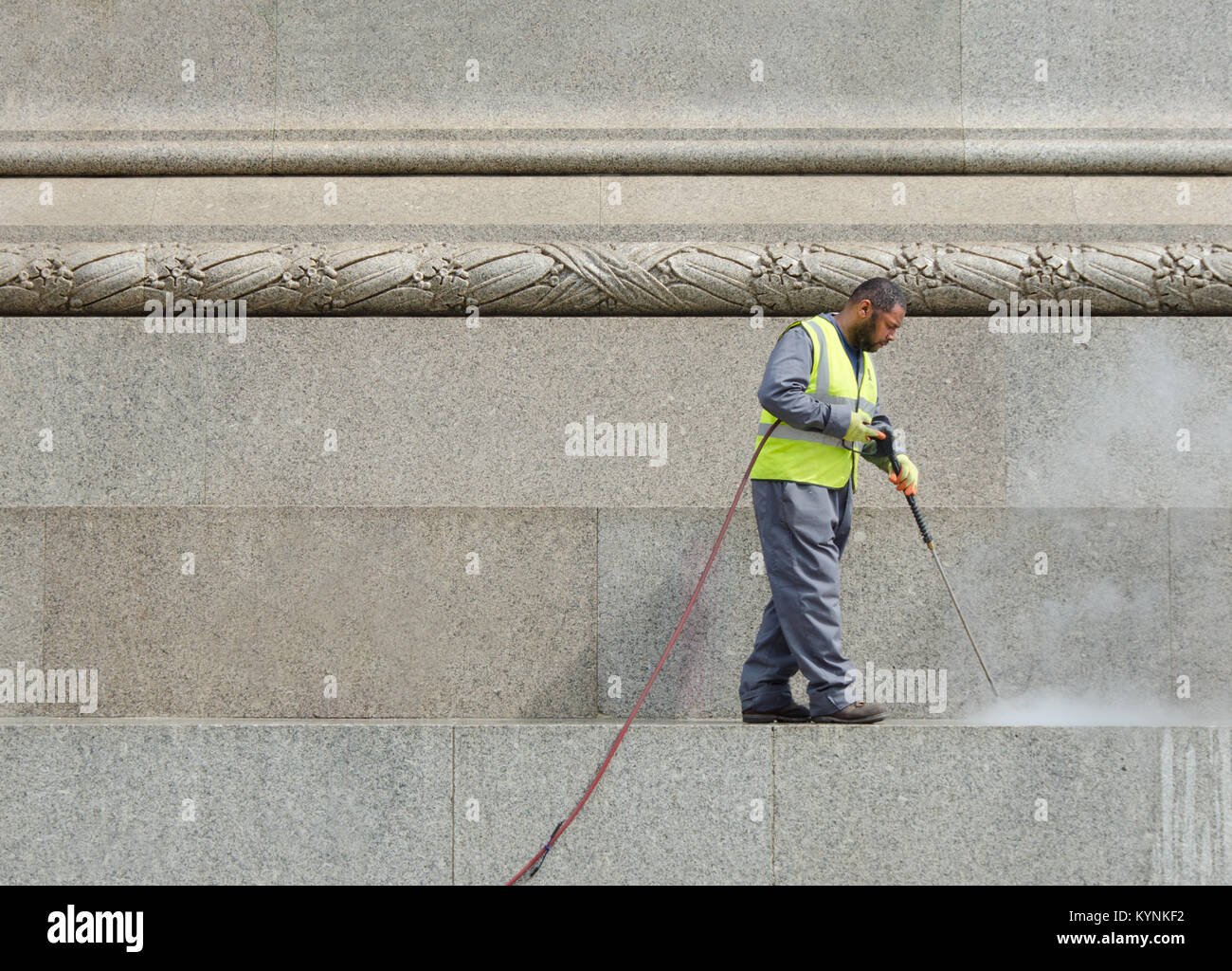 London, England, UK. Man cleaning the base of Nelson's Column with a pressure washer - Stock Image