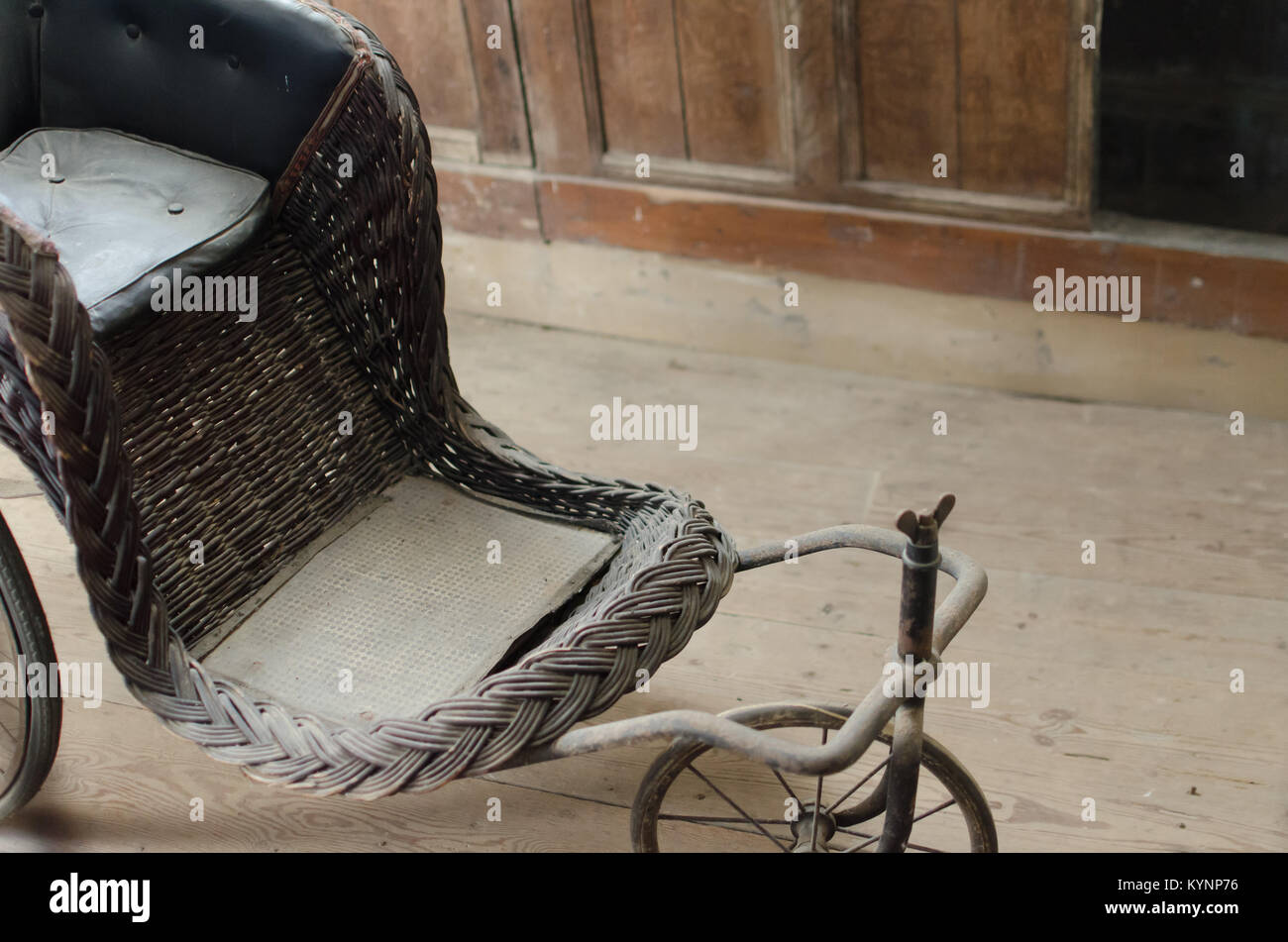 A vintage/retro antique wheelchair, sitting gathering dust in an old  abandoned house. - Vintage Wheelchair Stock Photos & Vintage Wheelchair Stock Images
