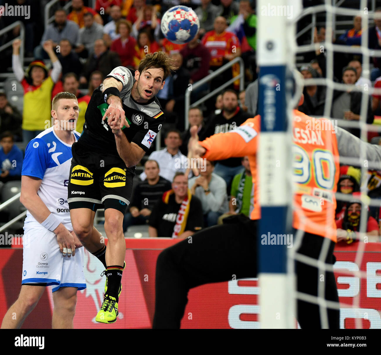 Germany's Uwe Gensheimer (L) throws at the goal of Slovenia's Urban Lesjak during the handball European - Stock Image
