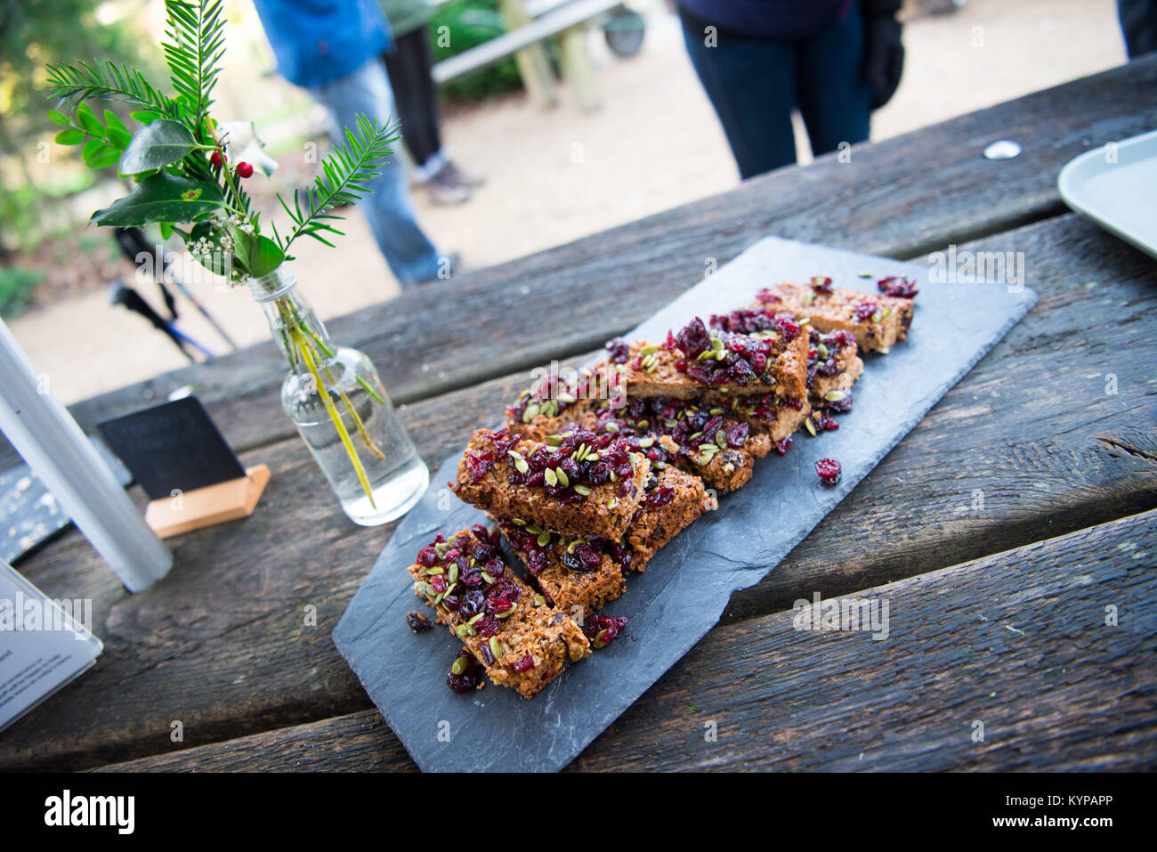 Piles of healthy homemade oat flapjack served on a slate board on a picnic bench for National Trust walkers on a - Stock Image