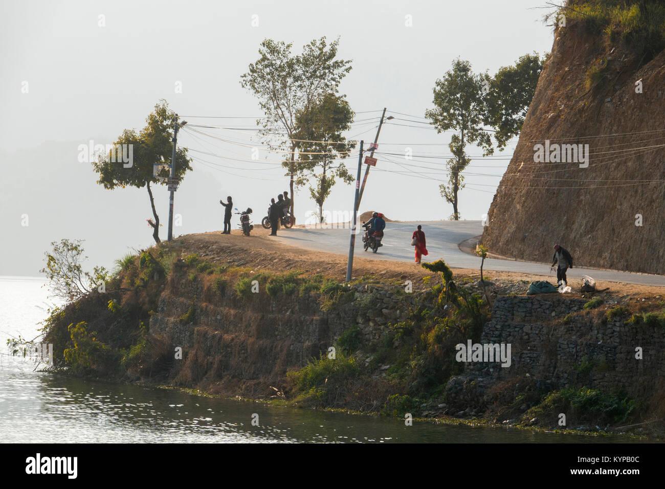 People walking on road around Phewa Lake, Pokhara, Nepal - Stock Image