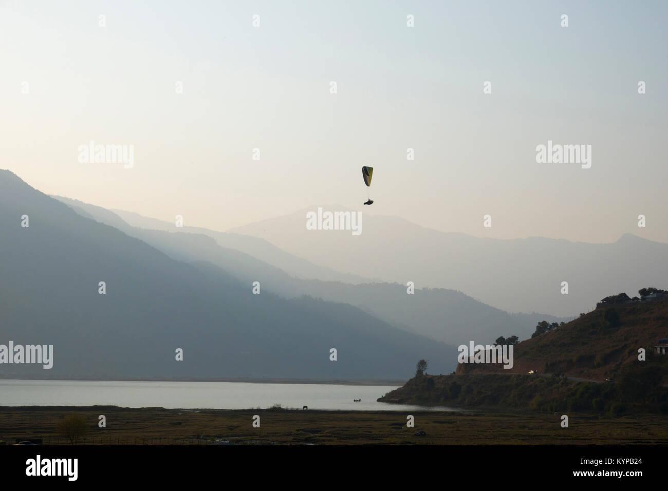 Solo paragliding above Phewa Lake in Pokhara, Nepal - Stock Image