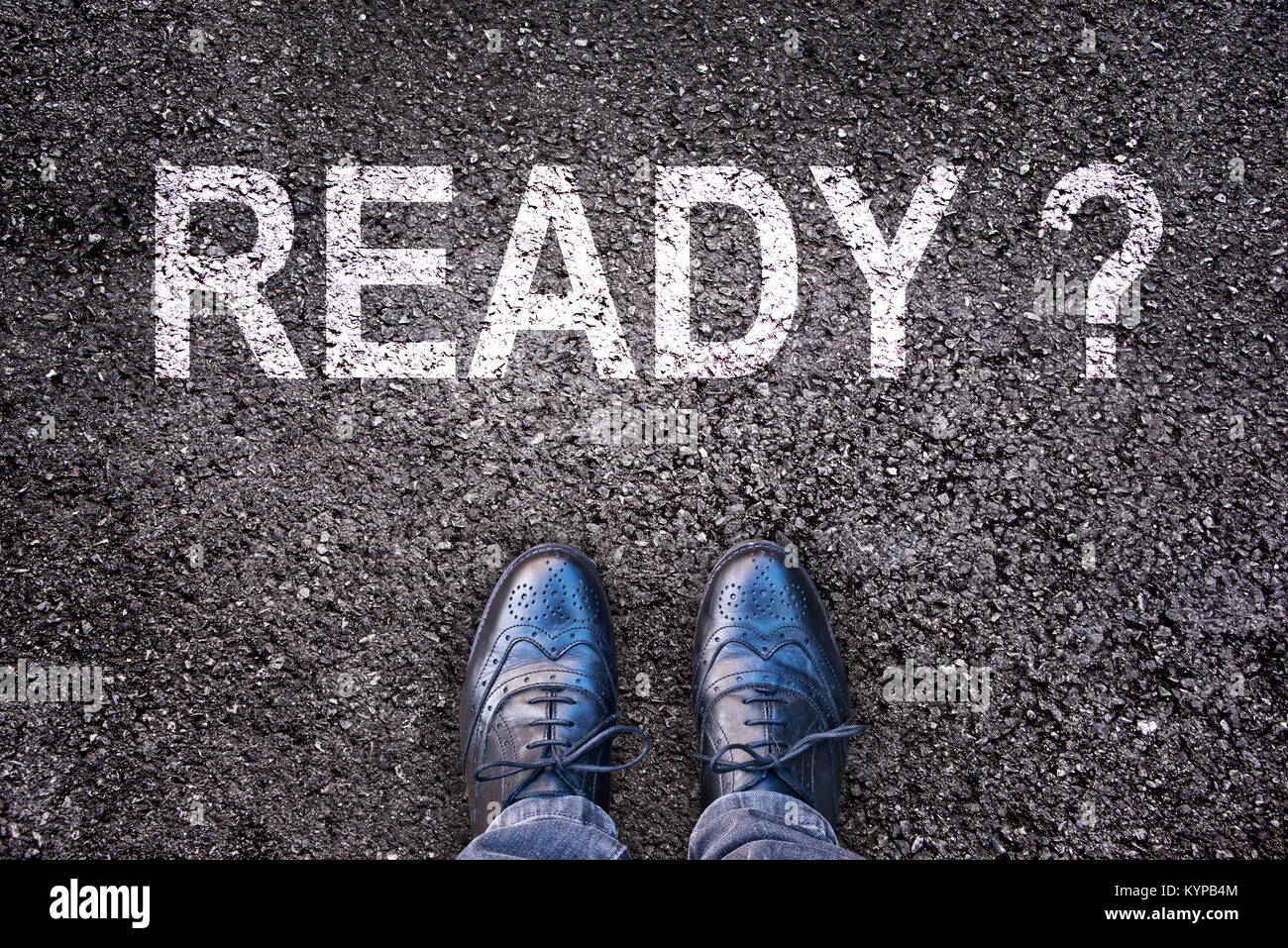 Question Ready ? written on an asphalt road with legs and shoes - Stock Image