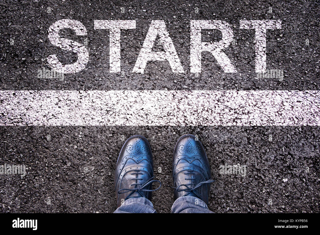 Word Start written on an asphalt road with legs and shoes - Stock Image