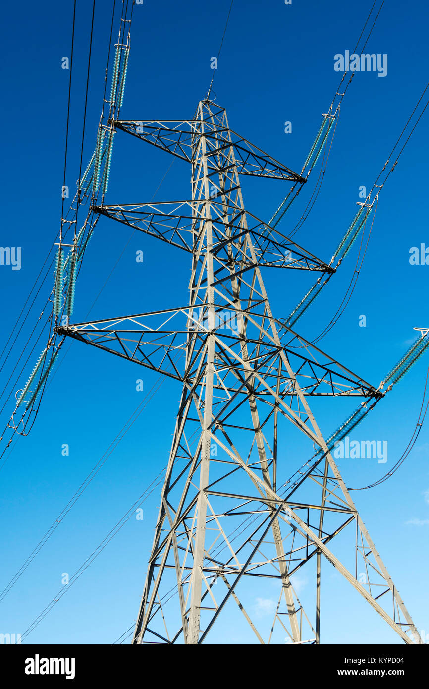 Electricity pylon against blue sky shot from below, England, UK - Stock Image