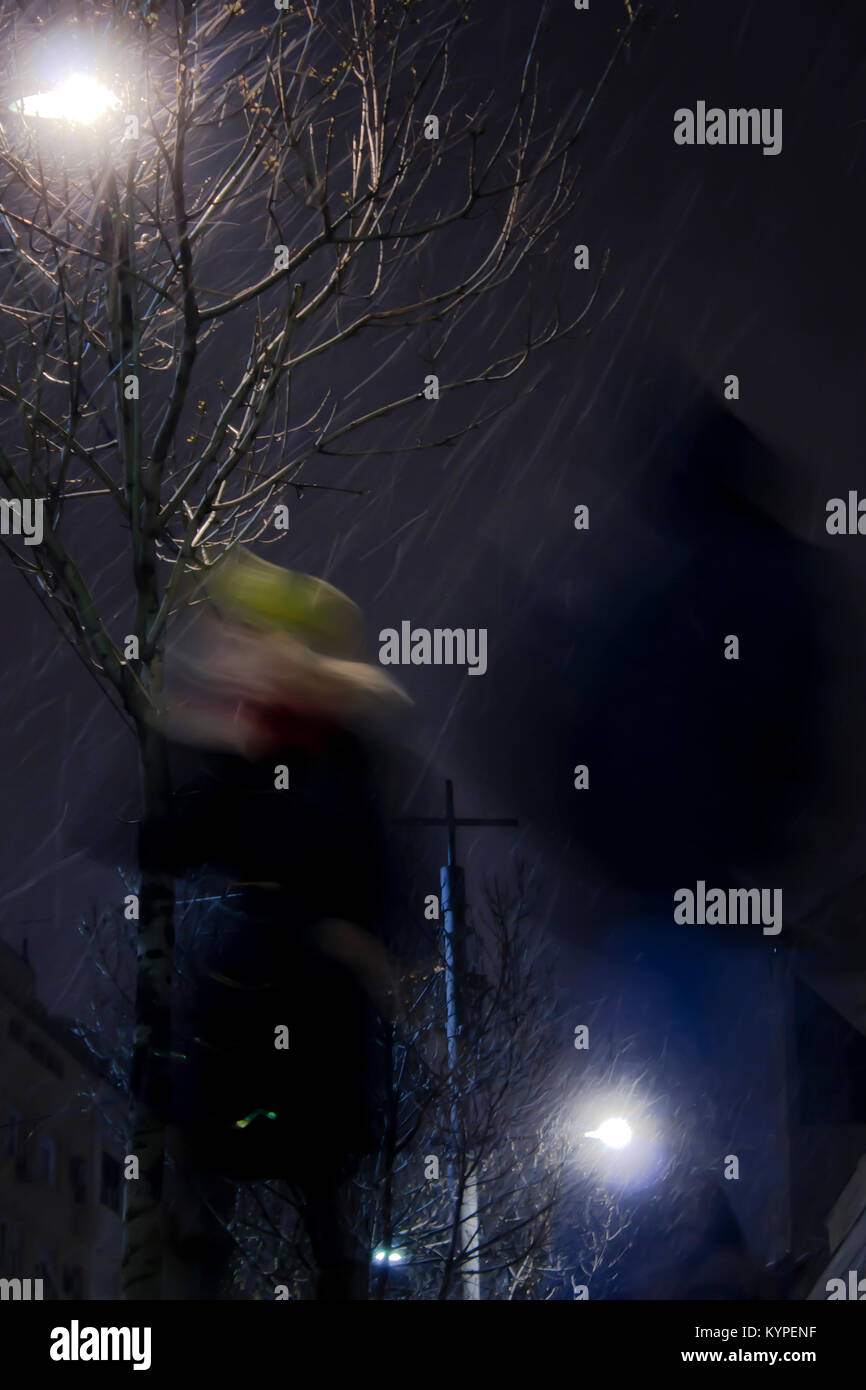 Blurry people walking in snowy and windy city streets in winter night , low angle view - Stock Image