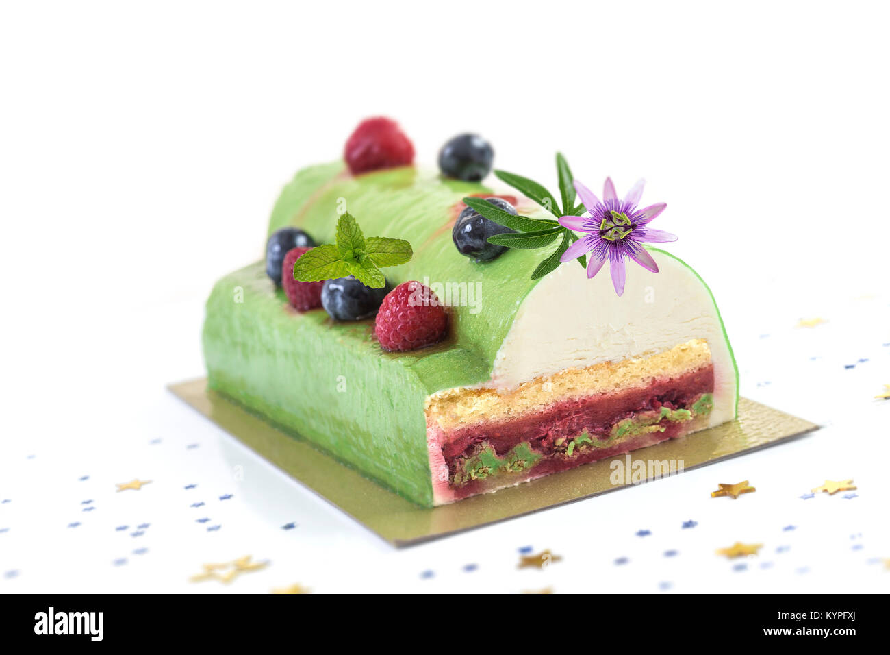 Pistachio Raspberry Yule Log decorated with fresh raspberries, blueberry, and pasion flower on white background. - Stock Image
