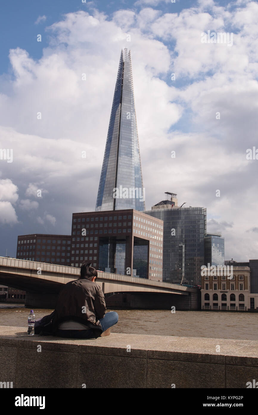 A young woman sitting on the wall on the bank of the River Thames opposite The Shard by London Bridge with her bottle - Stock Image