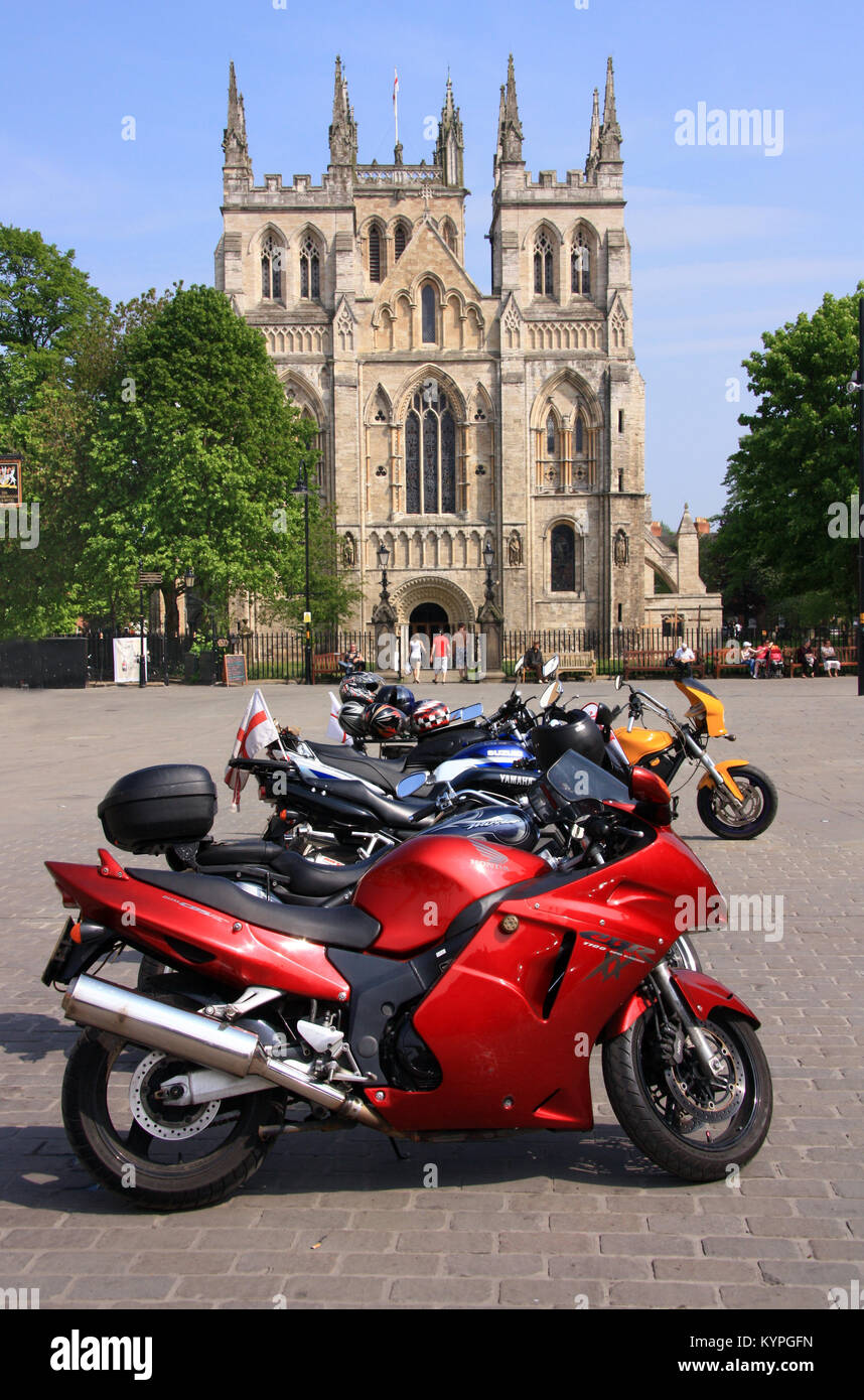 Motor cycles parked in front of the abbey at Selby in north Yorkshire England UK - Stock Image