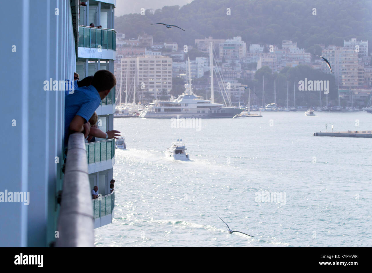 Passengers on a luxury cruise ship looking out of their balcony onto the harbour in Palma de Majorca, Spain - Stock Image