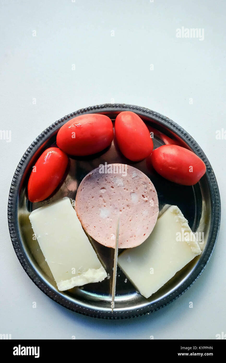 Simple Meze of Graviera Cheese, Garlic Salami and Tomatoes - Stock Image