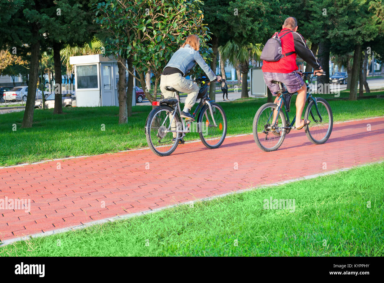 Active senior age and urban life - a couple of city dwellers a man and a woman at an age go on bicycles on the bike - Stock Image