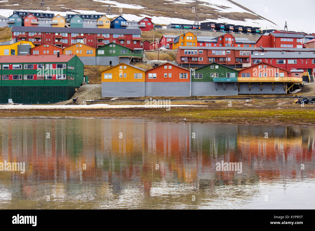 Colourful residential houses reflected in water in coal mining town of Longyearbyen, Spitsbergen Island, Svalbard, - Stock Image