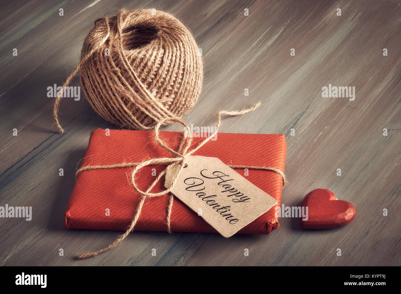 Wrapped gift tied up with cord, cardboard tag with text 'Happy Valentine' and a wooden heart on rustic wooden - Stock Image