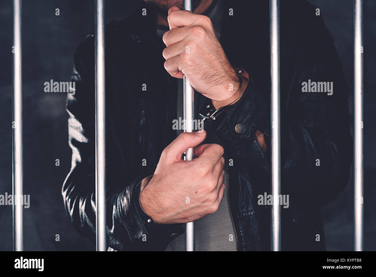 Handcuffed man behind prison bars. Arrested criminal male person imprisoned. - Stock Image