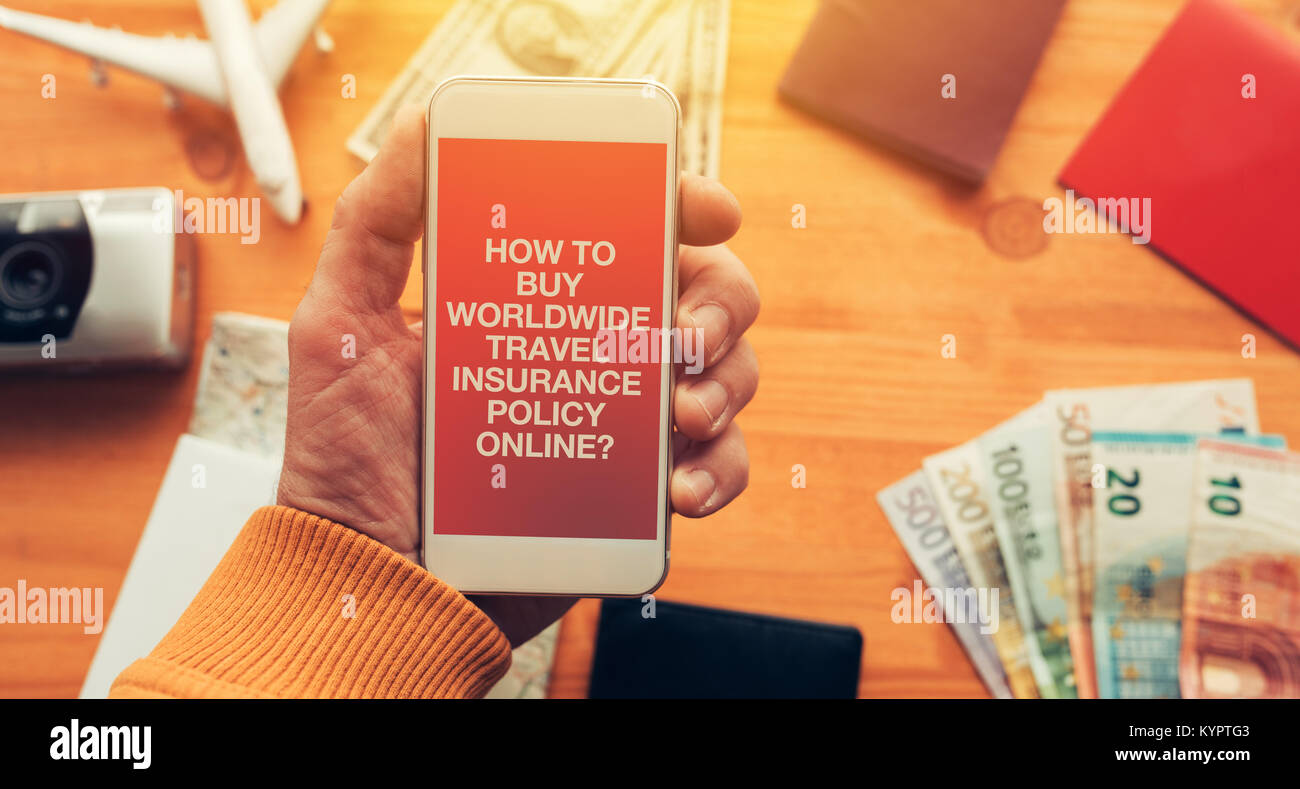 Worldwide travel insurance policy online mobile app. Man holding smartphone with mock up application screen related - Stock Image