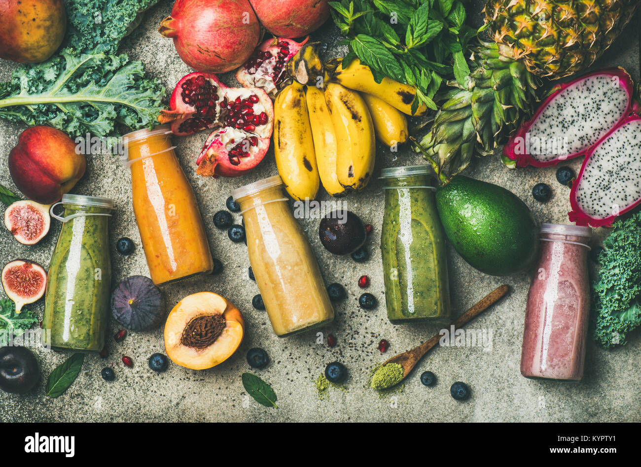 Flat-lay of colorful smoothies in bottles with fresh tropical fruit and superfoods on concrete background, top view. - Stock Image