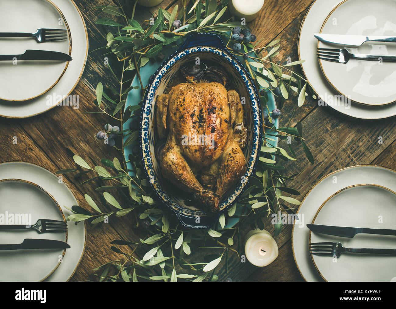 Flat-lay of whole roasted chicken in tray for Christmas eve celebration, plates and candles over rustic wooden background, - Stock Image
