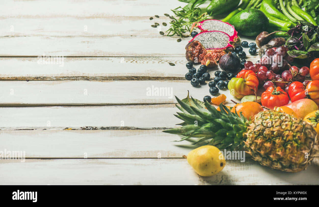 Helathy raw vegan food cooking background. Fresh fruit, vegetables, greens, superfoods over white wooden table, - Stock Image