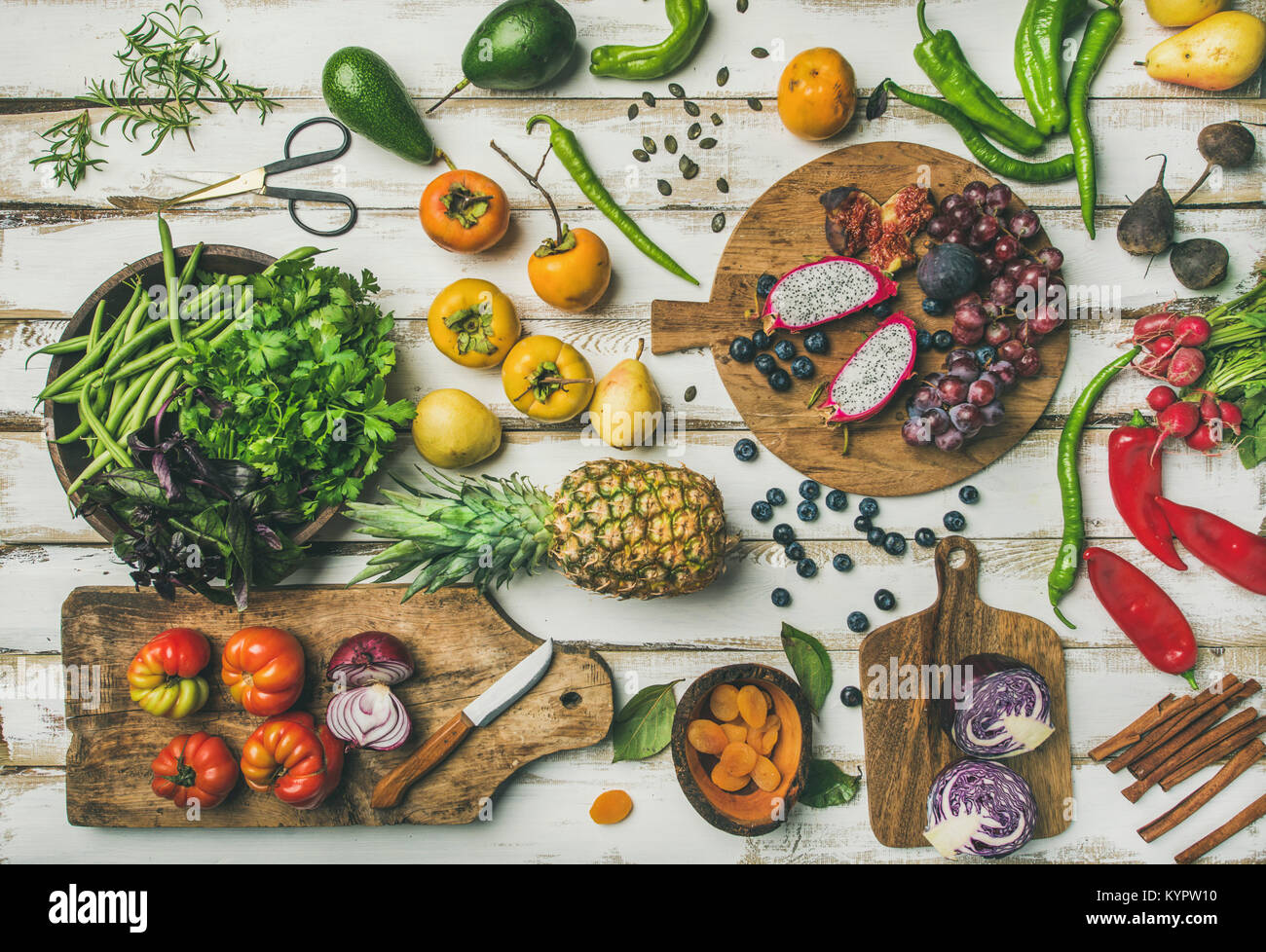 Helathy raw vegan food cooking background. Flat-lay of Fresh fruit, vegetables, greens and superfoods on boards Stock Photo