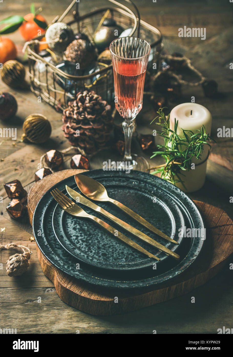 Christmas or New Years eve holiday table setting. Plates, silverware, champaigne in glass, candle and toy festive - Stock Image