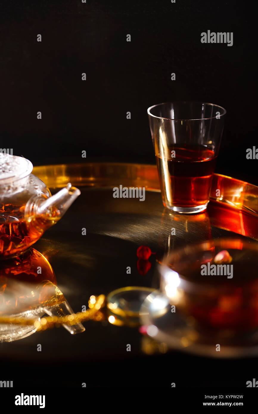 Small glass teapot and glasses with hot black tea, dried rose petals, pocket magnifier on golden chain on golden - Stock Image