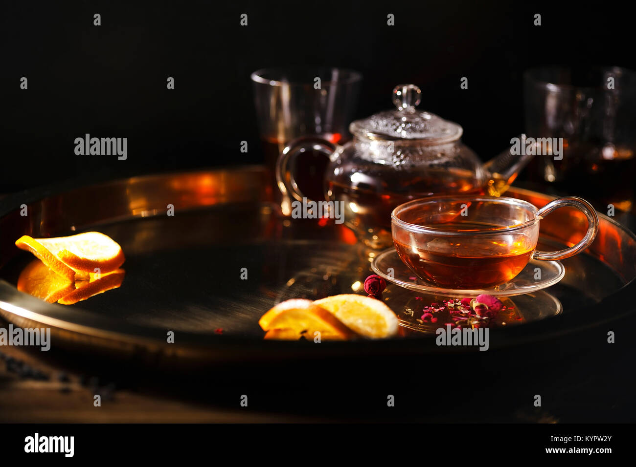 Small glass teapot and glasses with hot black tea, dried rose petals, pocket magnifier on golden chain, squeezed - Stock Image