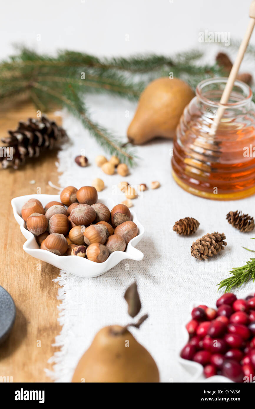 Nuts, pairs, cranberries and honey on a kitchen table - Stock Image