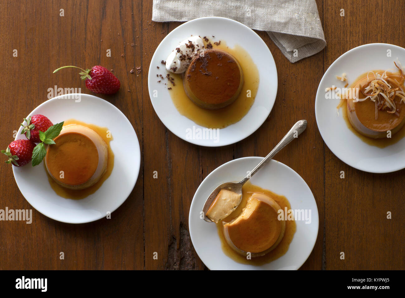 Assorted flavored individually plated flans photographed on a rustic wood surface with vintage silverware and linens. - Stock Image