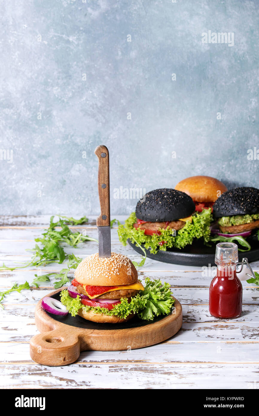 Set of homemade burgers in black and white buns with avocado, tomato sauce, lettuce, arugula, cheese, onion on wood - Stock Image