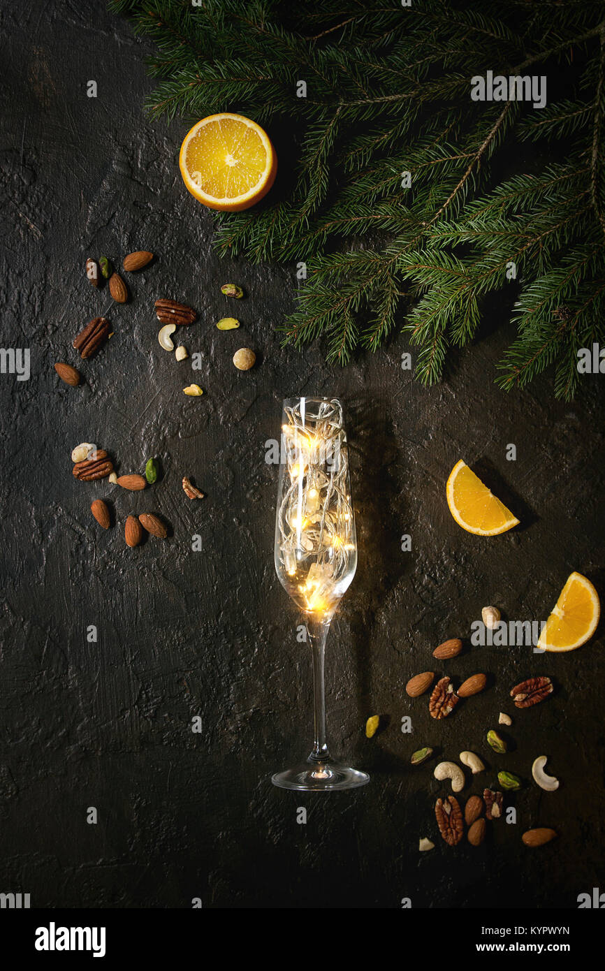 Christmas lights garland in champagne glass with nuts, orange, fir tree branches over dark texture background. Christmas - Stock Image