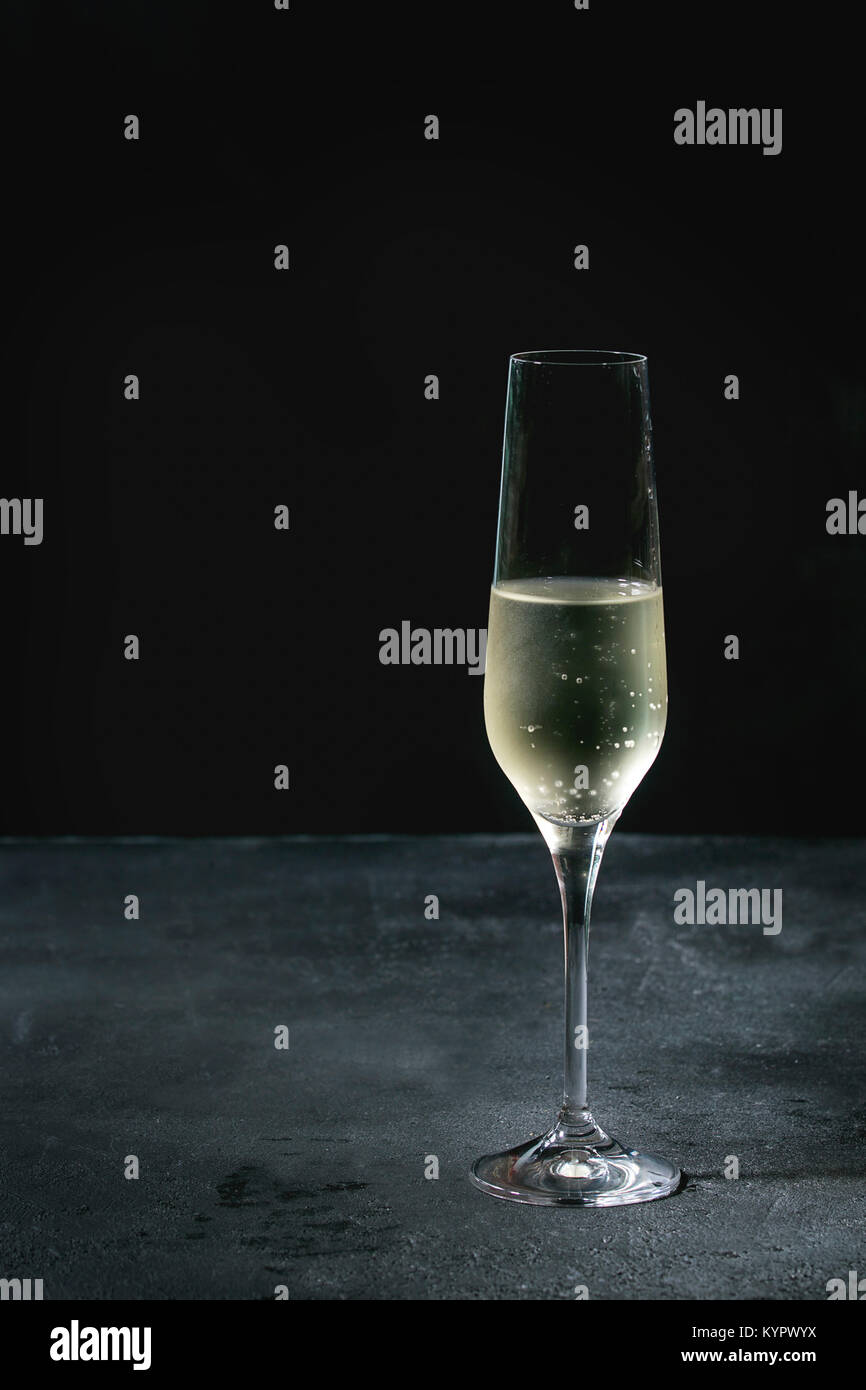 One glass of white champagne over dark texture background. Copy space - Stock Image