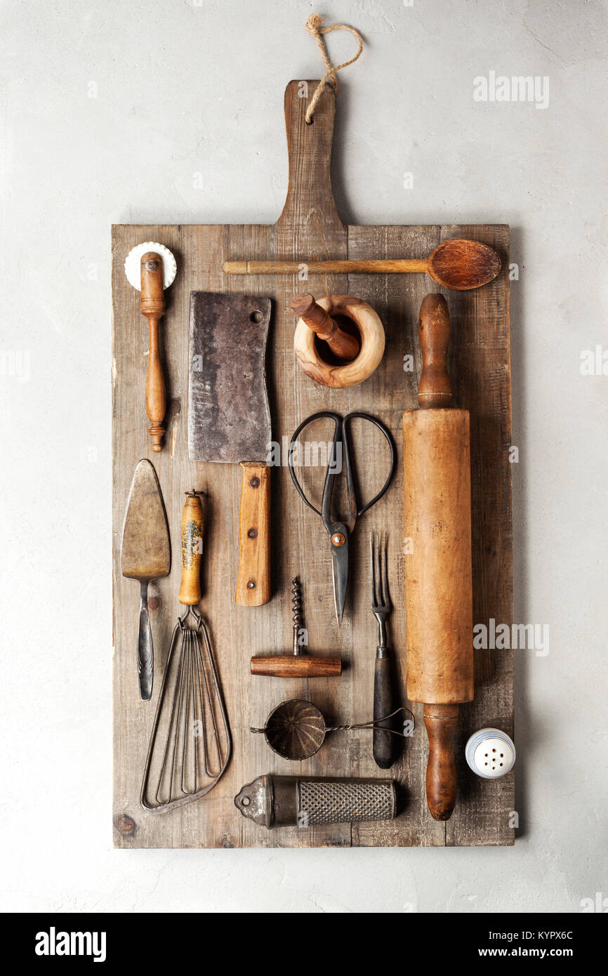 Top view of a group of vintage cooking utensils on a wood cutting board. - Stock Image